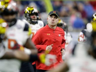 Maryland head coach DJ Durkin runs onto the field before the Quick Lane Bowl NCAA college football game against Boston College in Detroit.